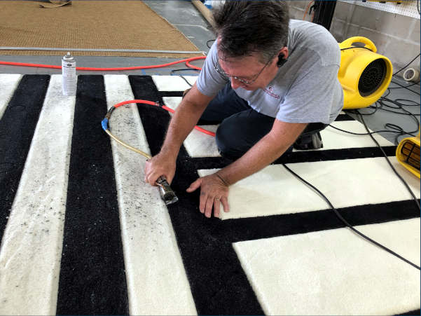 Bob Ford carving sharper lines in fabricated, custom rug