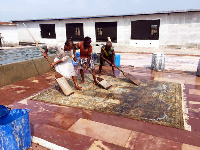 Washing a new rug at a factory in India
