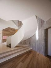 Winding staircase backed by flooring on the wall